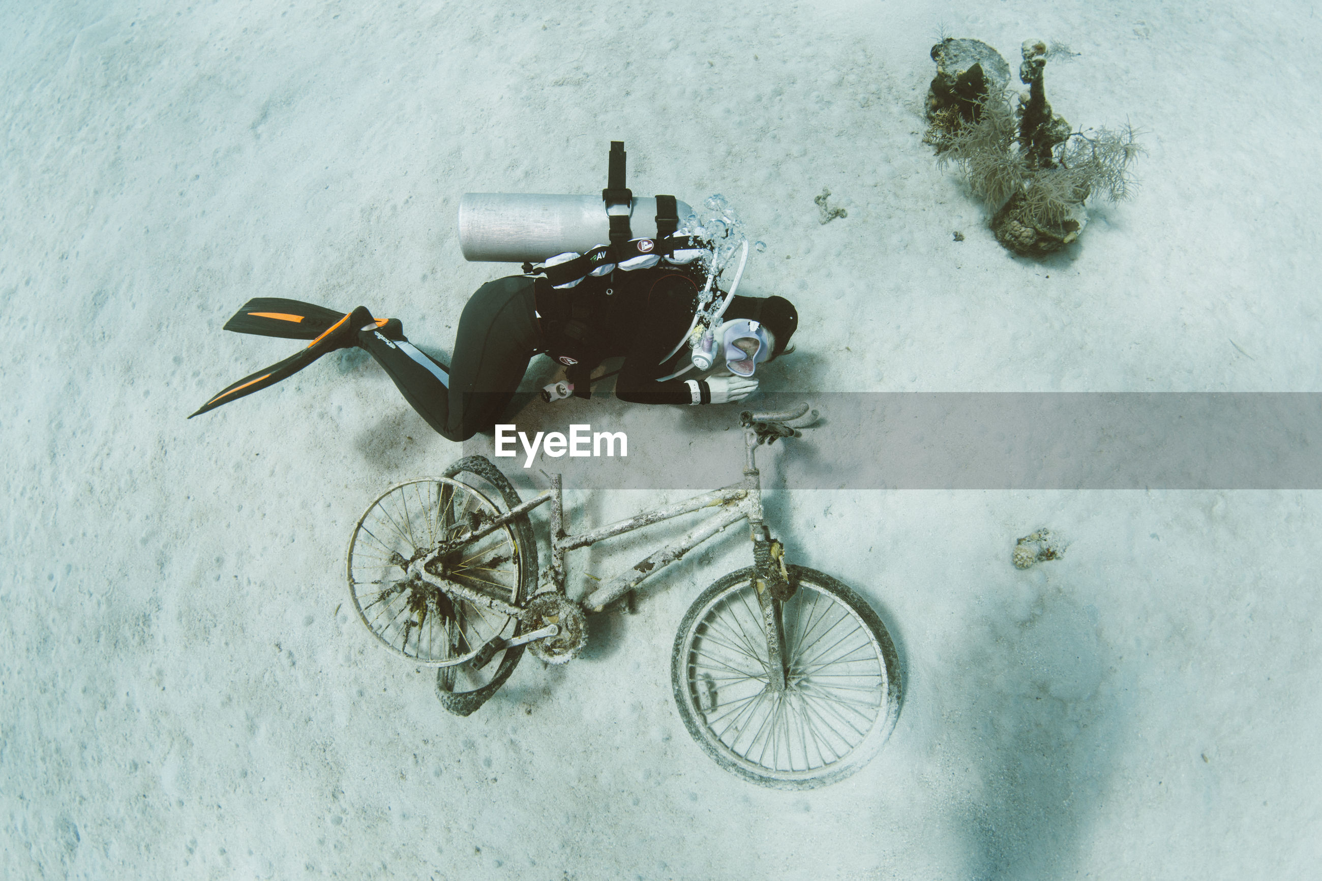 High angle view of scuba diver by abandoned bicycle in sea