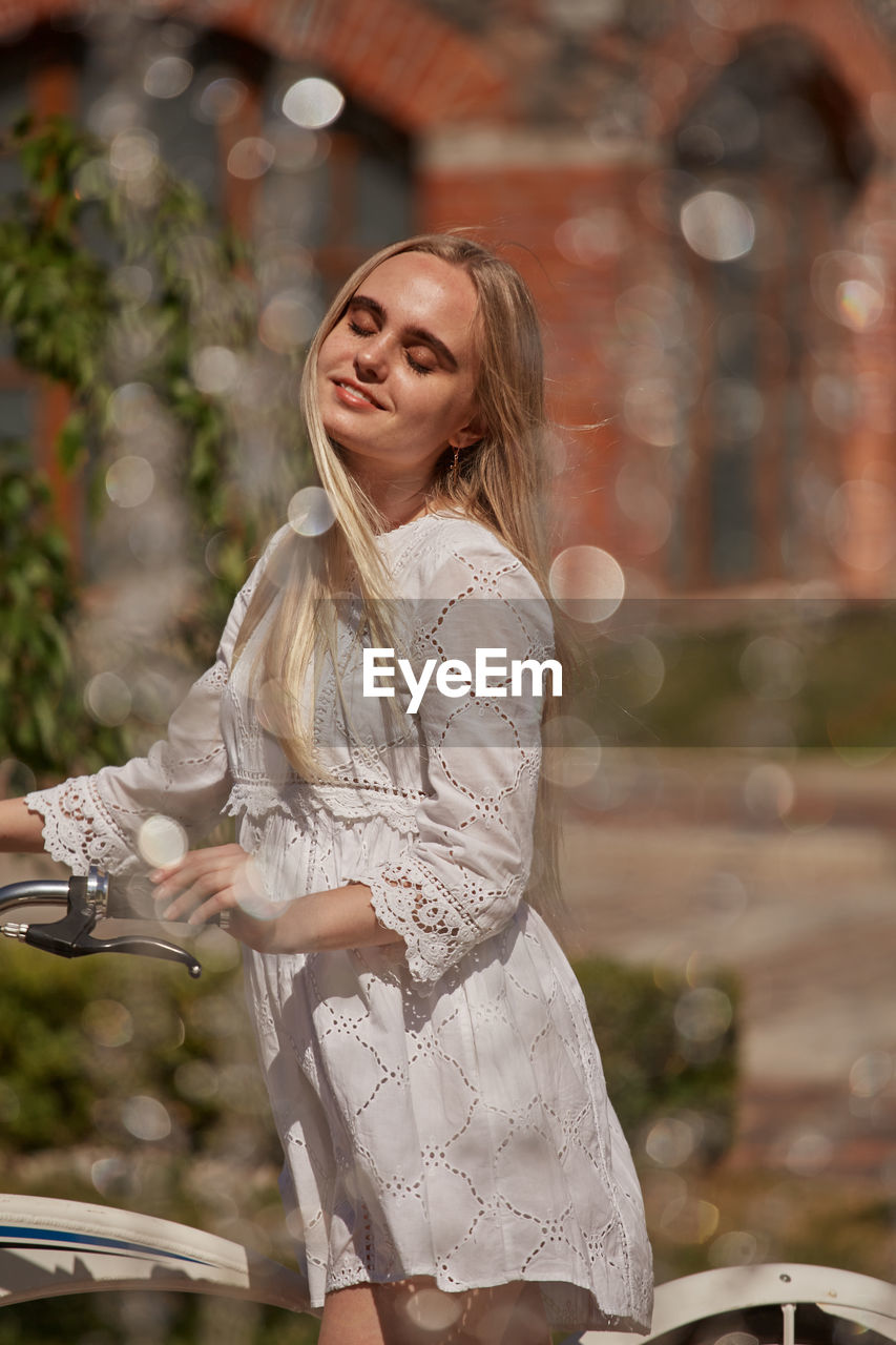 Pretty blond girl in white dress with bike near fountain in sunny light