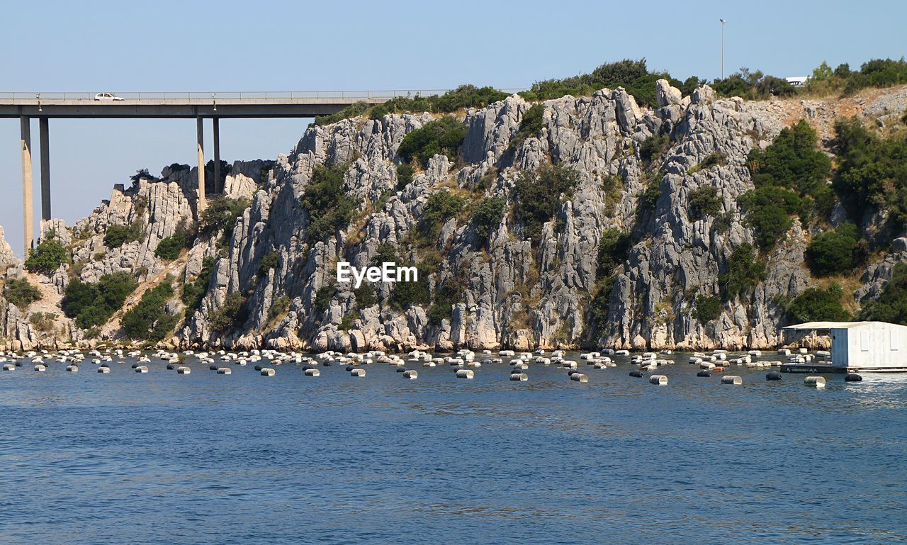 water, sea, waterfront, sky, architecture, built structure, nature, transportation, day, mountain, no people, tranquil scene, scenics - nature, beauty in nature, rock, connection, tranquility, land, bridge, outdoors