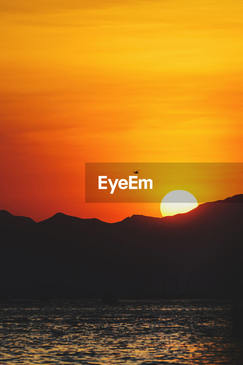 sunset, sky, scenics - nature, beauty in nature, orange color, silhouette, water, waterfront, tranquil scene, tranquility, mountain, sun, sea, idyllic, nature, non-urban scene, no people, animal themes, outdoors, romantic sky