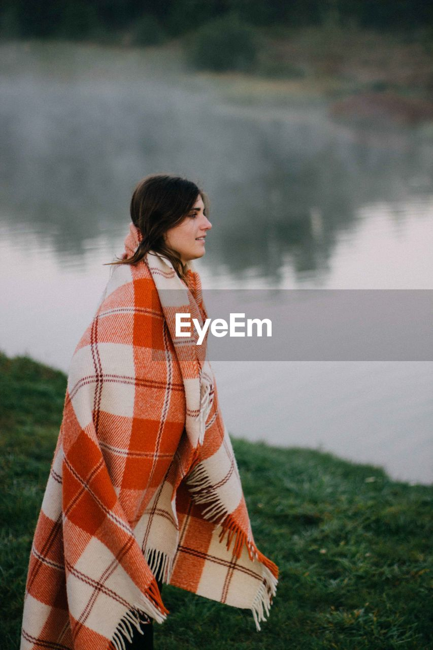 Young Woman With Blanket Standing On Lakeshore