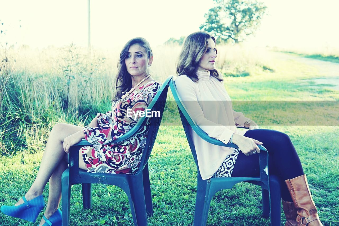 Women sitting back to back on chair over field at yard