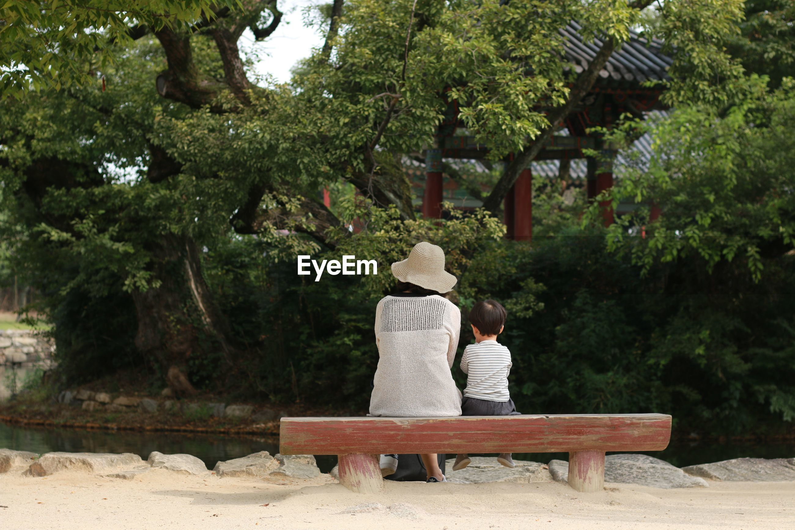 Rear view of mother and son sitting on bench at park