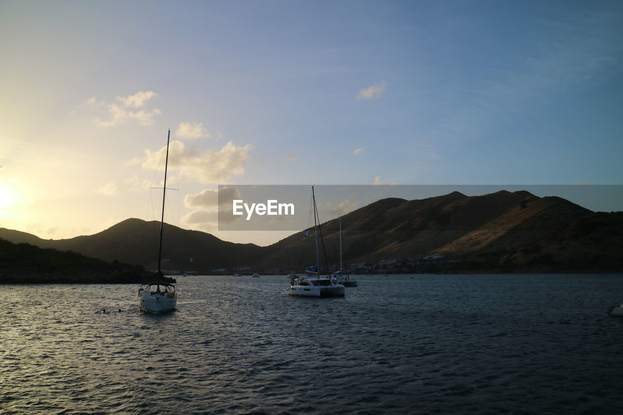 nautical vessel, water, transportation, sky, mountain, mode of transportation, waterfront, beauty in nature, sailboat, cloud - sky, sea, tranquil scene, scenics - nature, tranquility, nature, sailing, mast, no people, sunset, mountain range, outdoors, yacht, passenger craft, luxury
