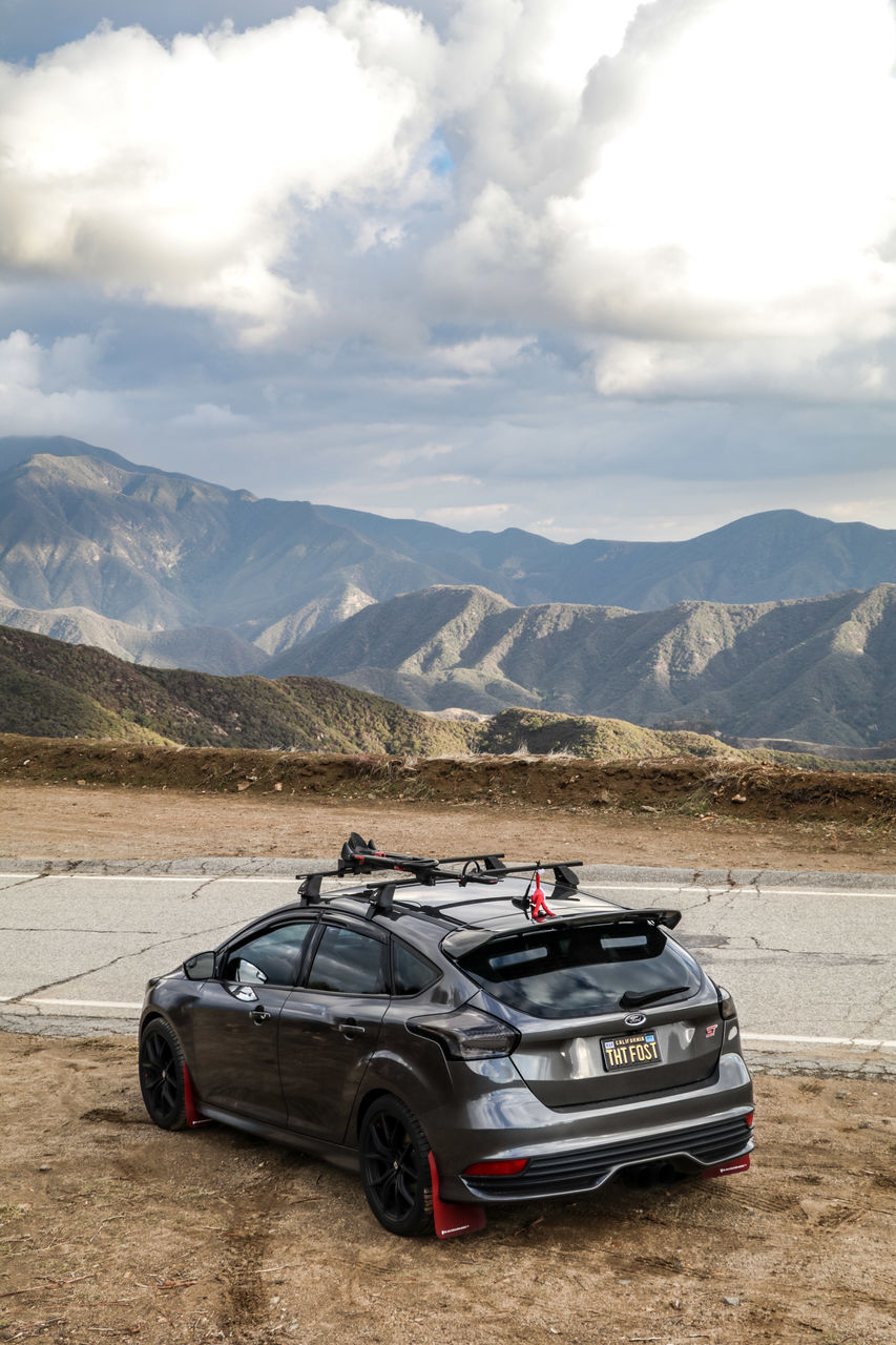 car, mode of transportation, mountain, motor vehicle, transportation, cloud - sky, sky, land vehicle, mountain range, day, scenics - nature, nature, beauty in nature, no people, non-urban scene, environment, travel, stationary, landscape, outdoors