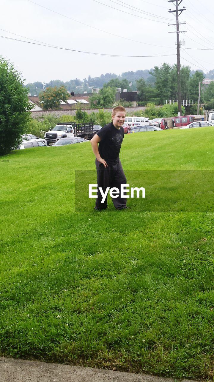 Full length of boy smiling on grassy field