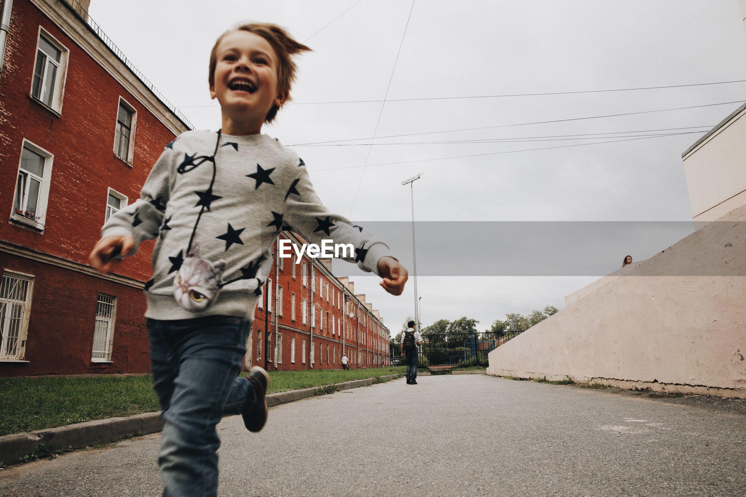 Happy boy running on road in city