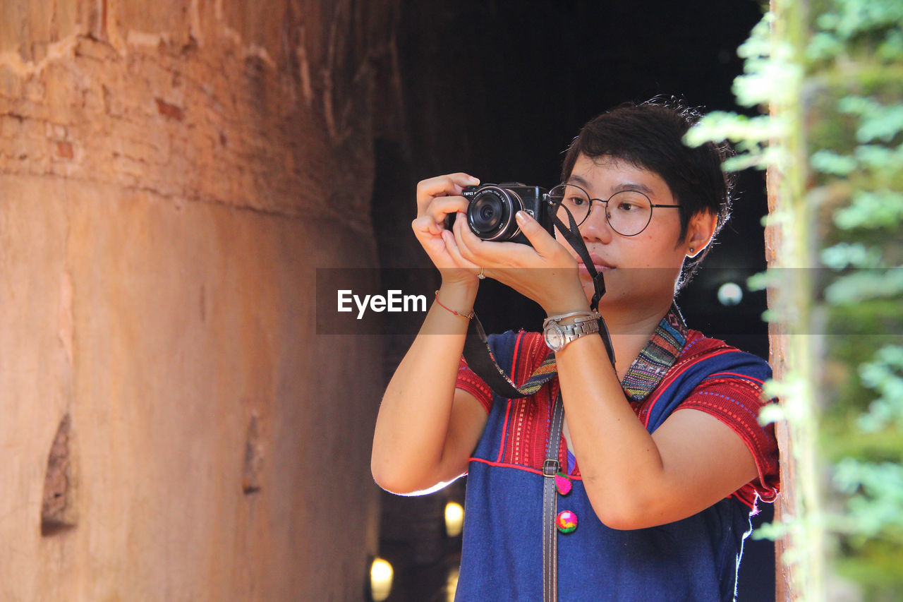 camera - photographic equipment, real people, technology, photography themes, one person, holding, casual clothing, leisure activity, photographic equipment, photographing, activity, lifestyles, focus on foreground, standing, young adult, digital camera, childhood, waist up, digital single-lens reflex camera, outdoors, photographer, hairstyle
