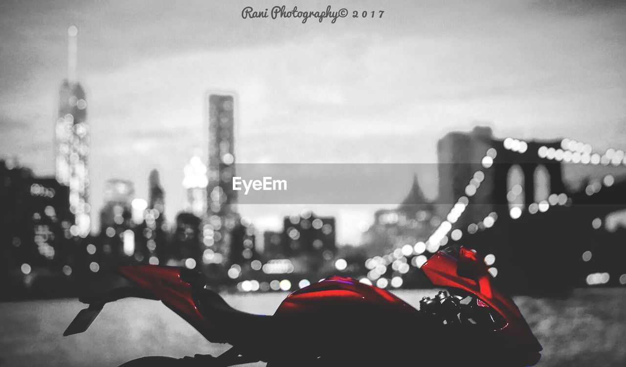 focus on foreground, city, building exterior, built structure, illuminated, real people, architecture, outdoors, one person, close-up, road, human hand, red, human body part, defocused, sky, day, people