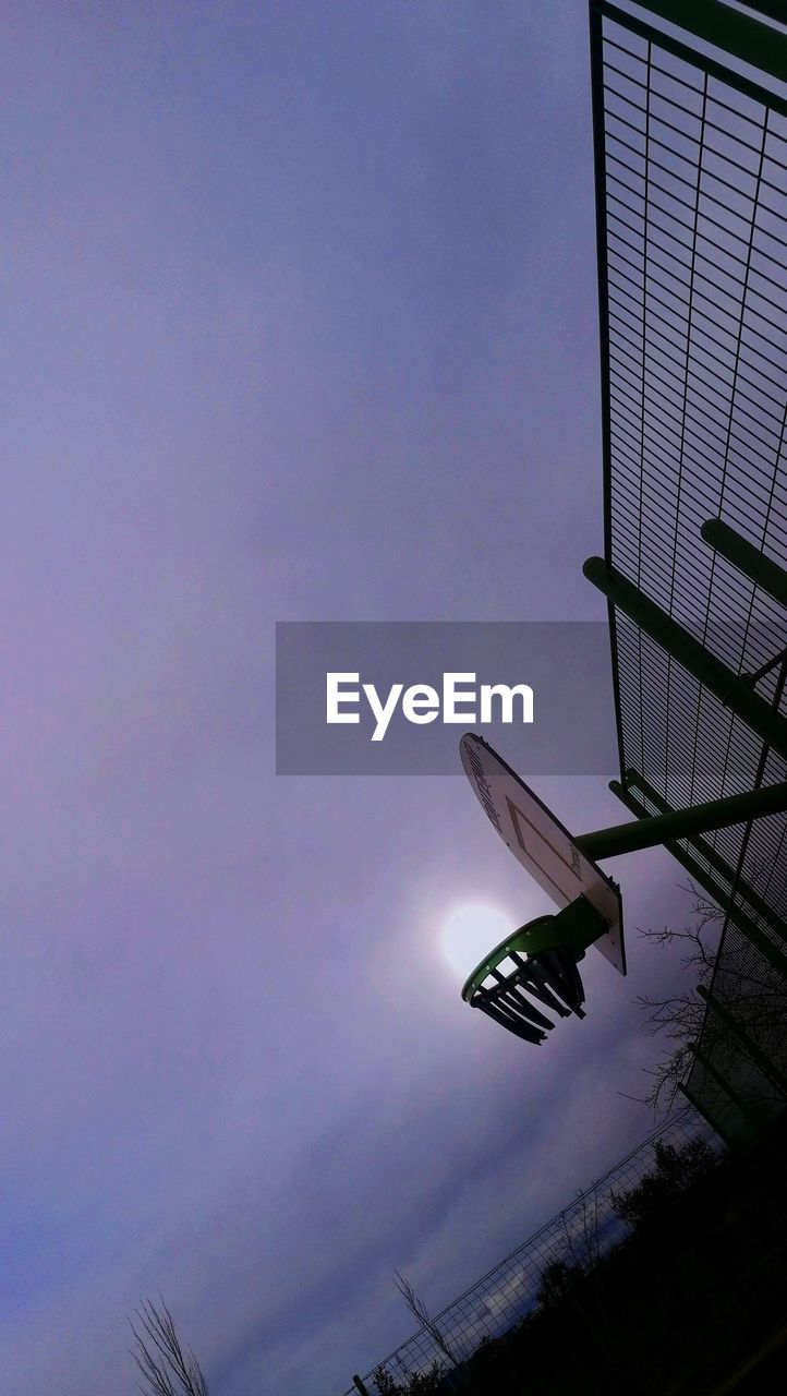 sky, low angle view, no people, architecture, nature, flying, mid-air, cloud - sky, built structure, outdoors, day, lighting equipment, tilt, building exterior, mode of transportation, transportation, dusk, air vehicle, blue, sunlight, skyscraper