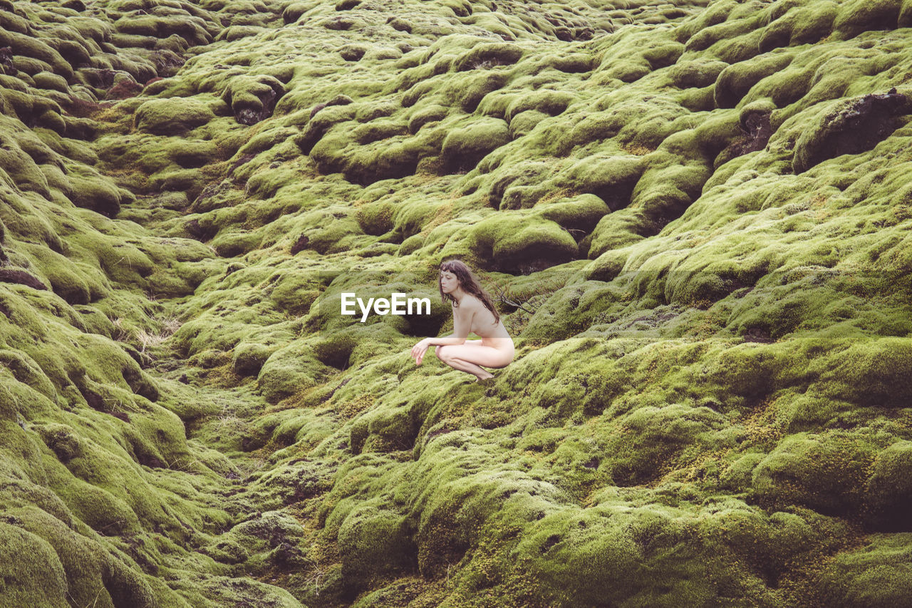 Side View Of Naked Woman Crouching On Mossy Rock