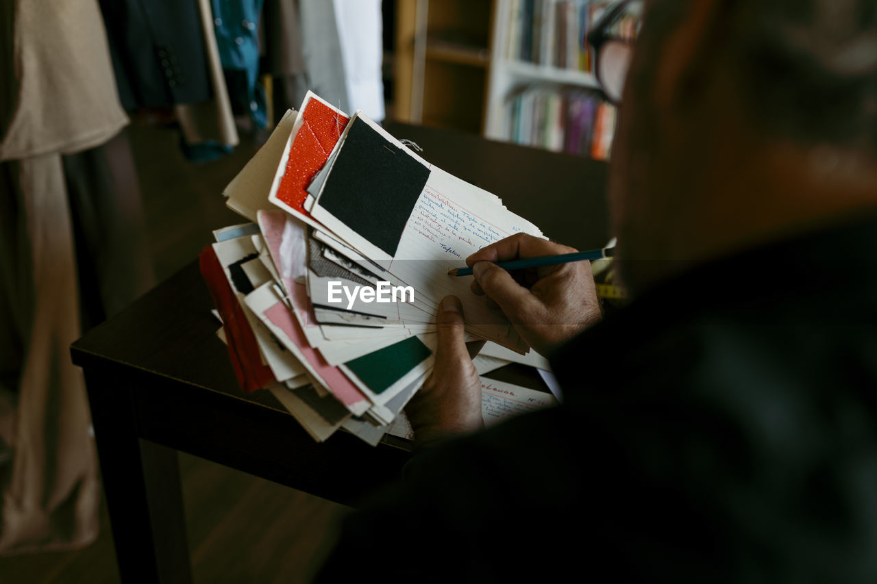 REAR VIEW OF MAN HOLDING BOOK AT HOME
