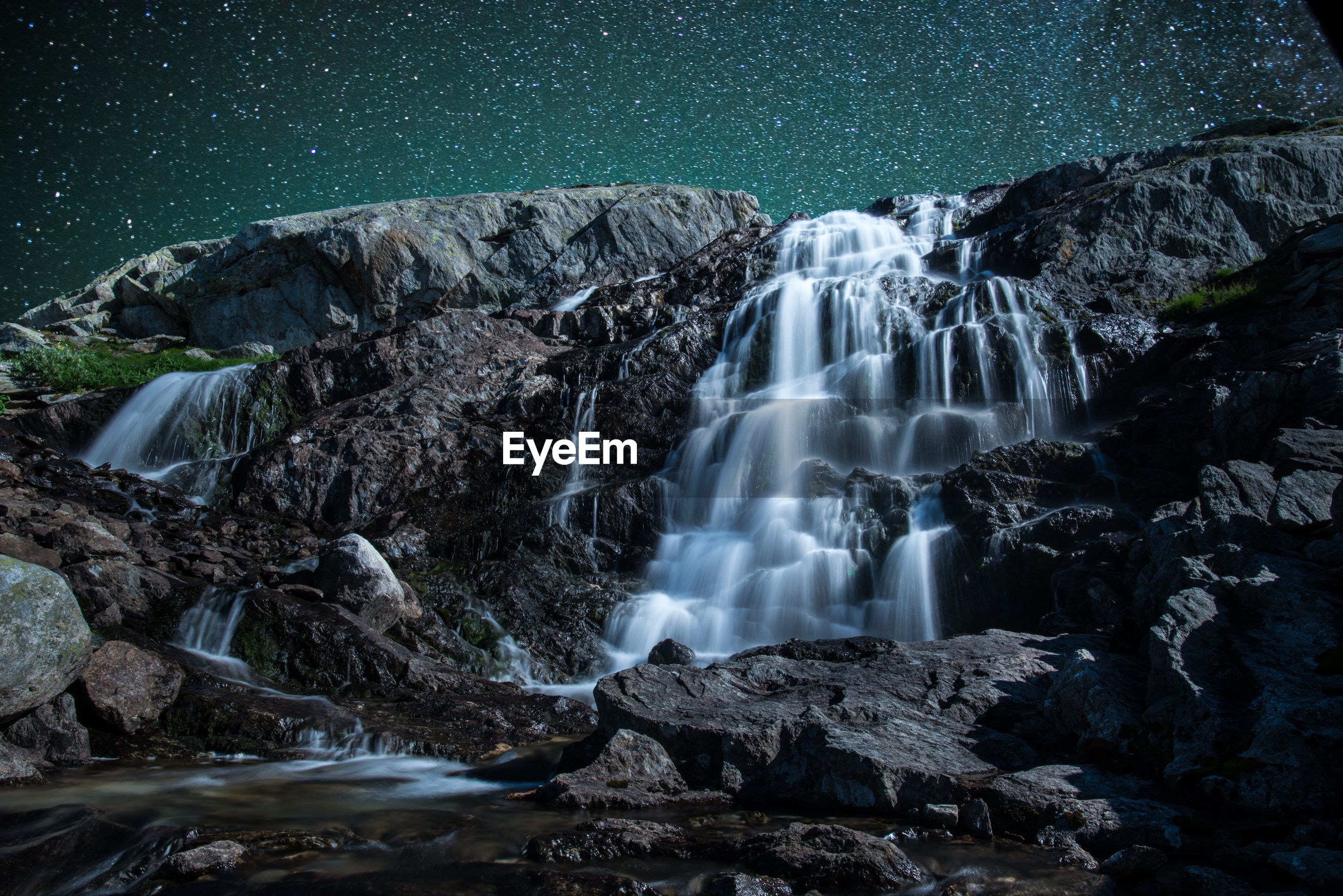 Low angle view of waterfall on rocky mountain against star field sky