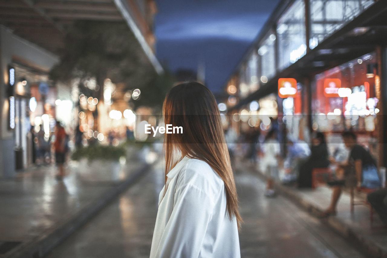 REAR VIEW OF WOMAN STANDING AT ILLUMINATED CITY AT NIGHT