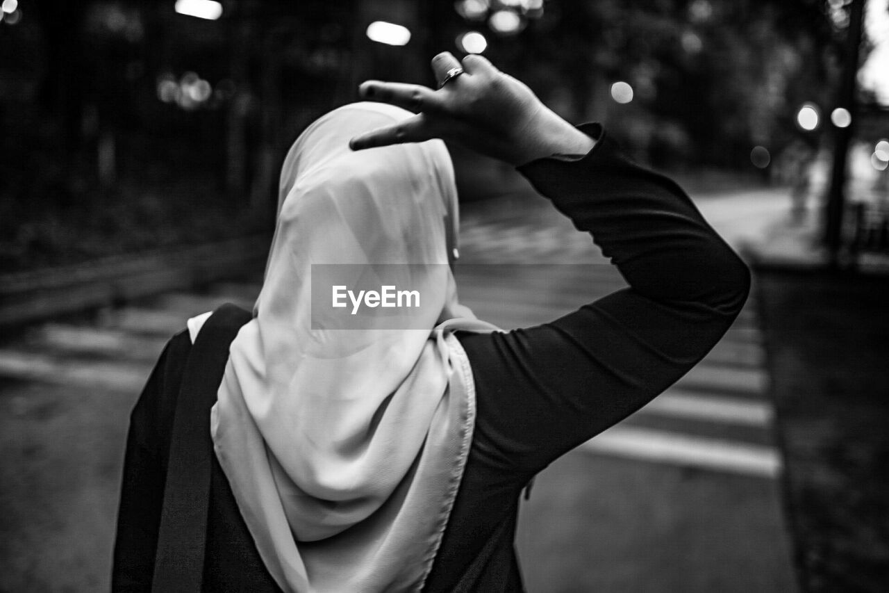 focus on foreground, one person, real people, waist up, lifestyles, leisure activity, rear view, day, women, casual clothing, hand, adult, standing, hood, unrecognizable person, clothing, outdoors, human hand, nature, arms raised, obscured face, hood - clothing, human arm, hairstyle, scarf