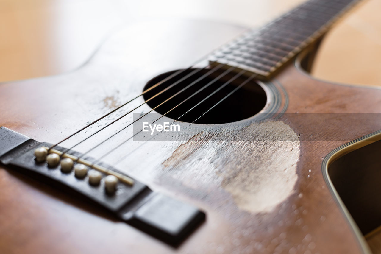 musical instrument, music, string instrument, guitar, musical equipment, musical instrument string, string, arts culture and entertainment, selective focus, close-up, acoustic guitar, indoors, no people, still life, fretboard, wood - material, table, sheet music, wind instrument, detail, electric guitar, silver colored