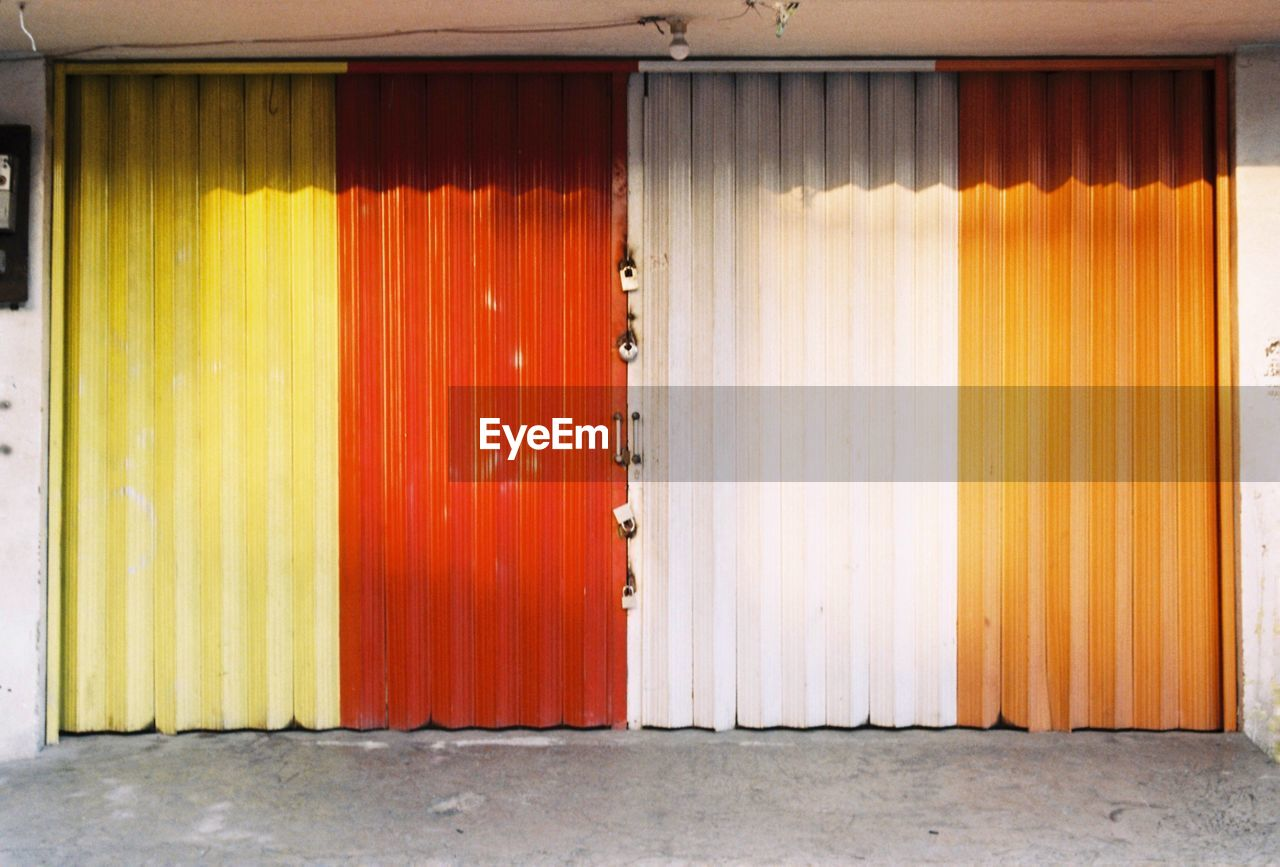 entrance, architecture, door, no people, built structure, security, day, multi colored, curtain, protection, building exterior, building, closed, safety, orange color, wall - building feature, outdoors, wood - material, metal, corrugated iron, iron, garage