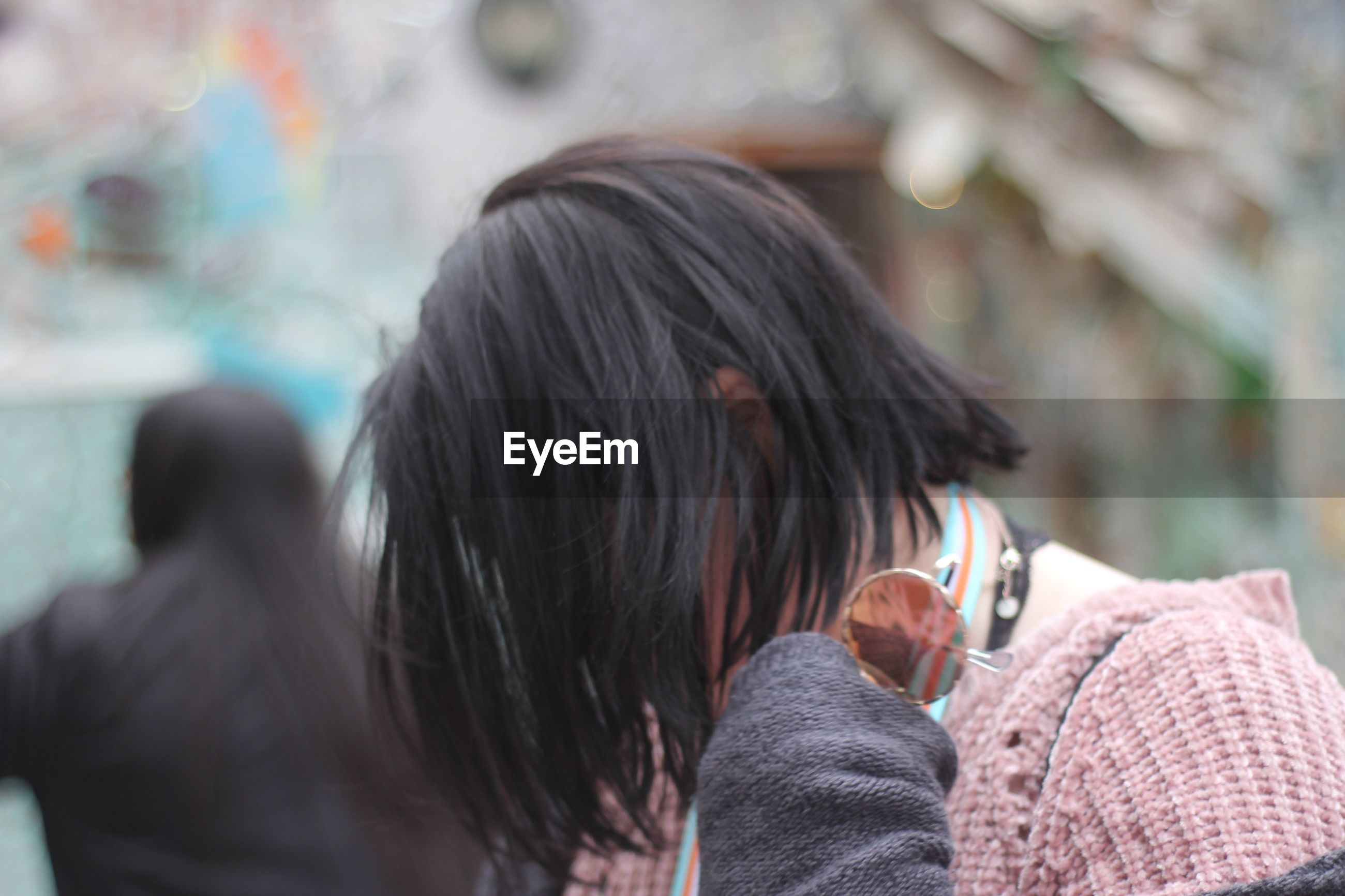 Side view of woman with face covered by hair in city