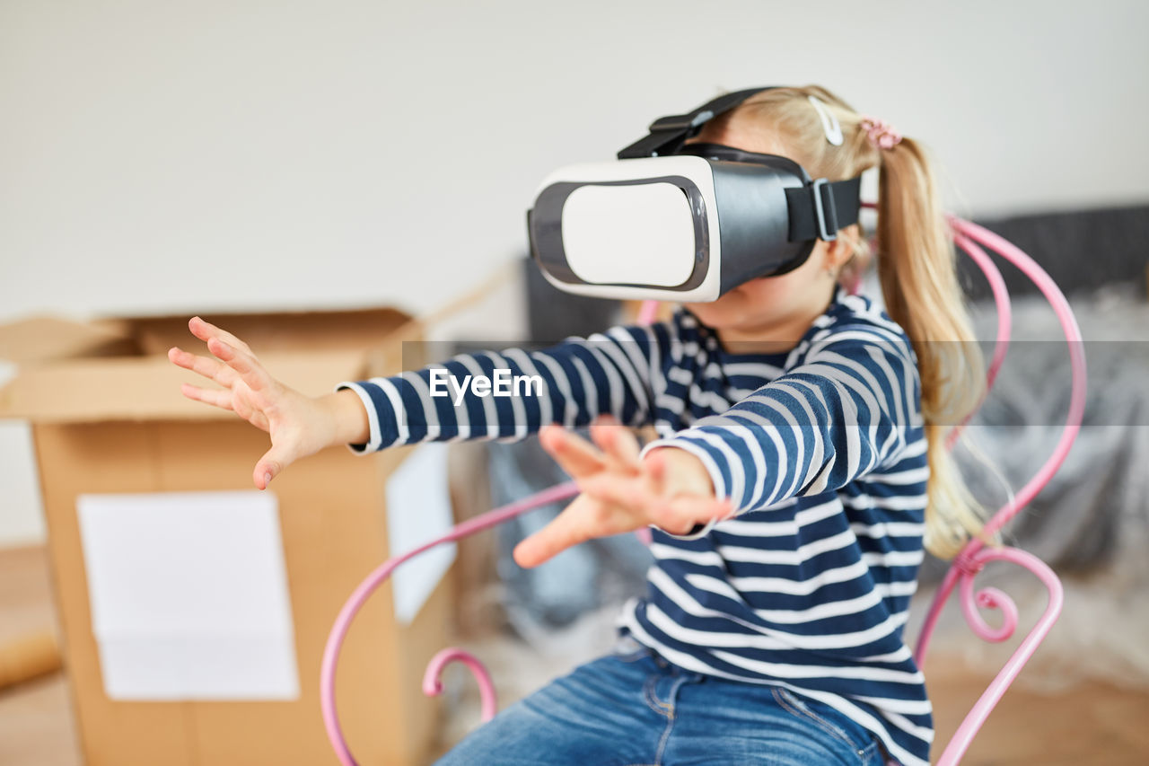 Girl looking through virtual reality simulator while sitting on chair