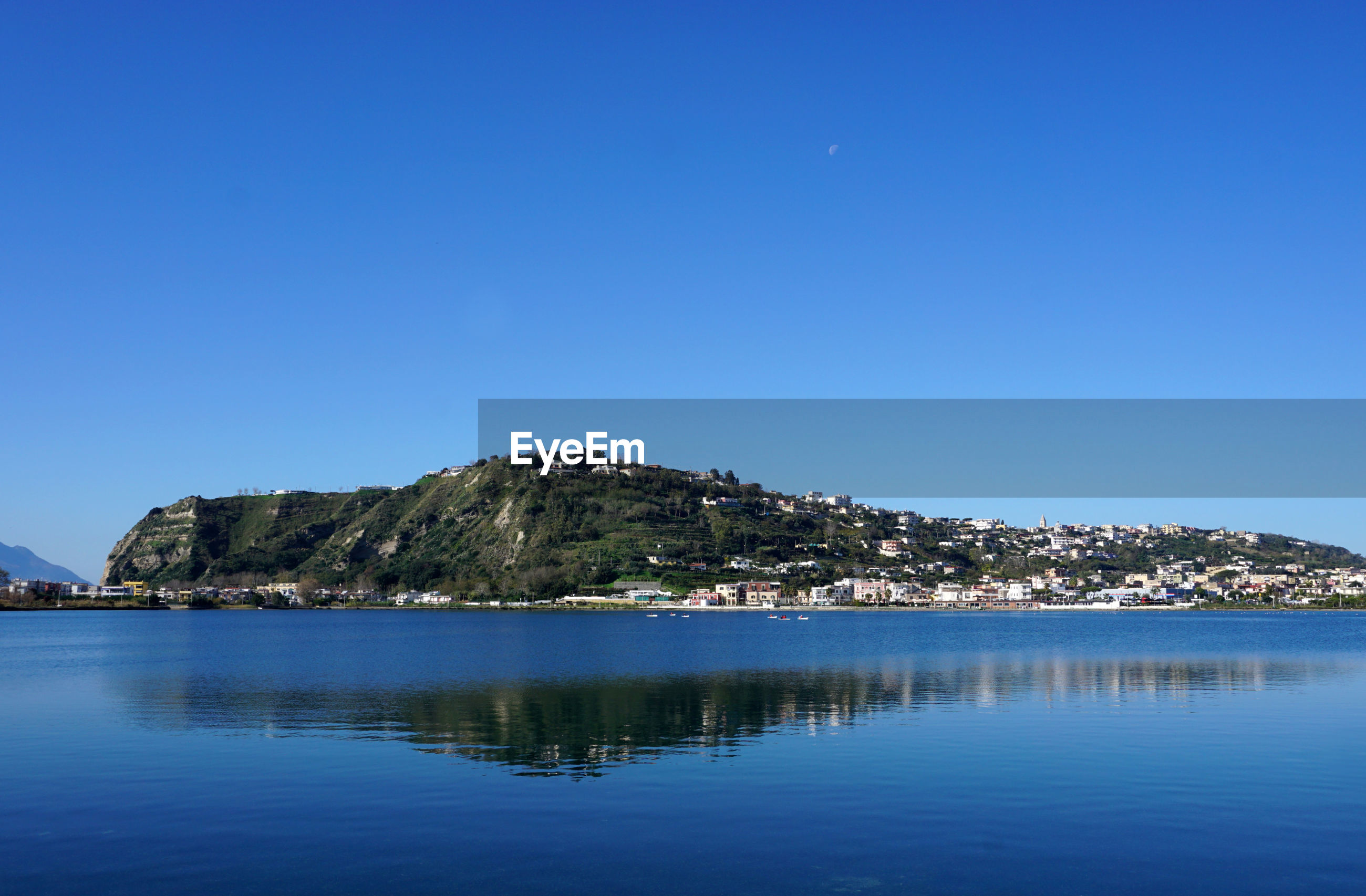 SCENIC VIEW OF SEA BY MOUNTAIN AGAINST CLEAR BLUE SKY