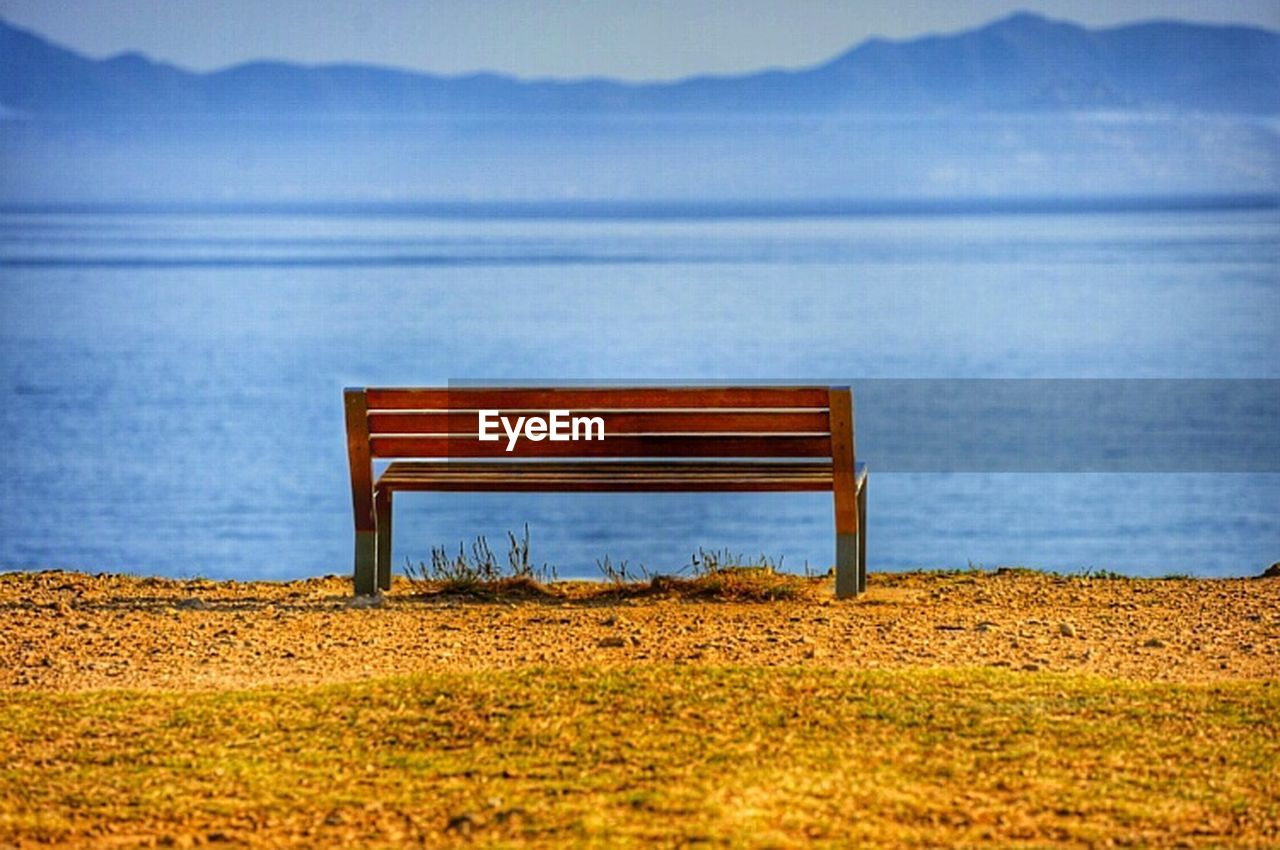bench, tranquility, scenics, tranquil scene, nature, empty, absence, water, idyllic, beauty in nature, day, relaxation, no people, sea, outdoors, beach, mountain, seat, sky