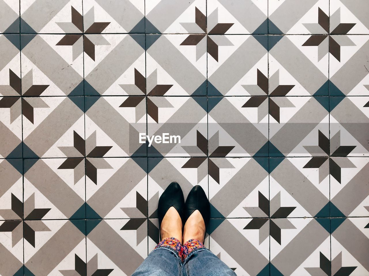 Low Section Of Woman Standing On Patterned Tiled Floor