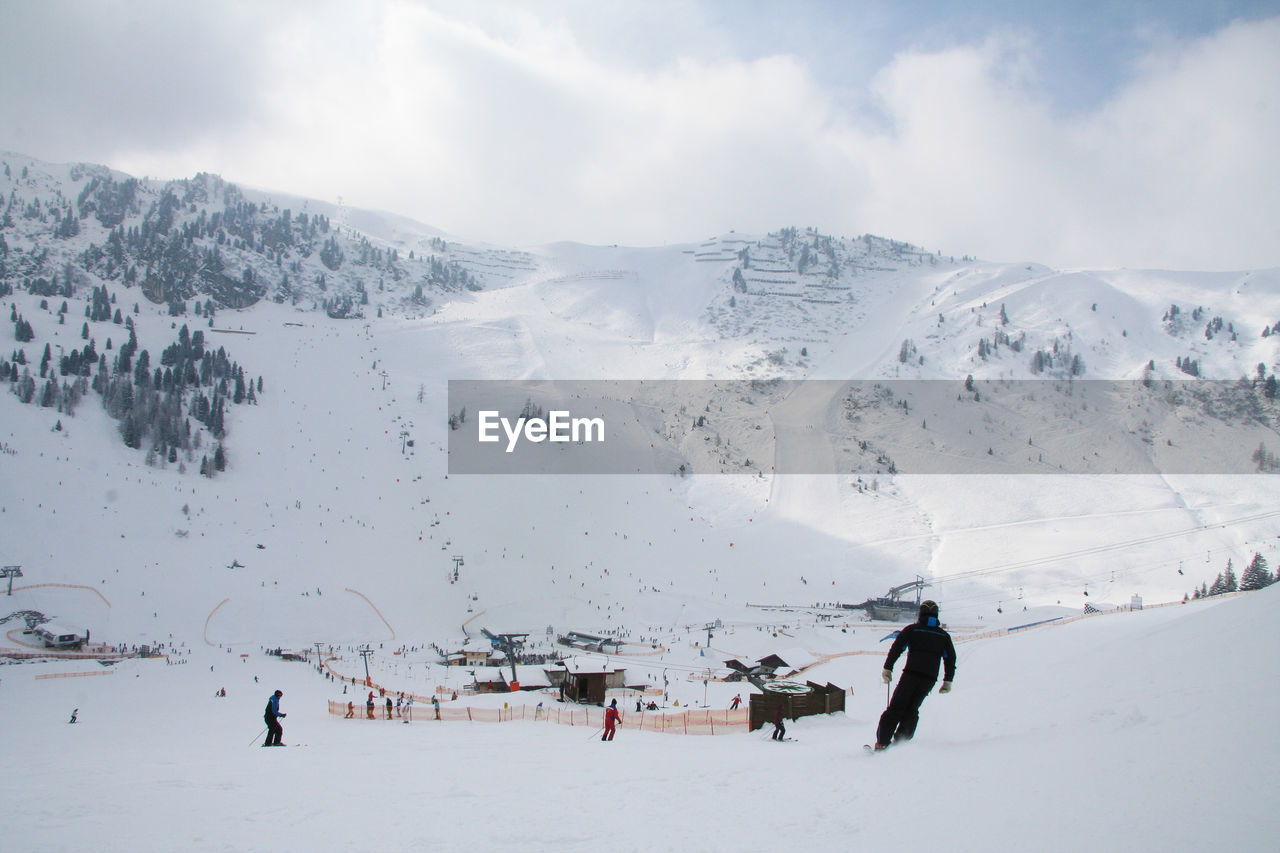 snow, winter, cold temperature, weather, nature, real people, beauty in nature, scenics, leisure activity, white color, mountain, outdoors, sky, day, cloud - sky, lifestyles, mountain range, tranquility, tranquil scene, vacations, men, landscape, snowcapped mountain, full length, adventure, two people, ski holiday, building exterior, tree, warm clothing, people