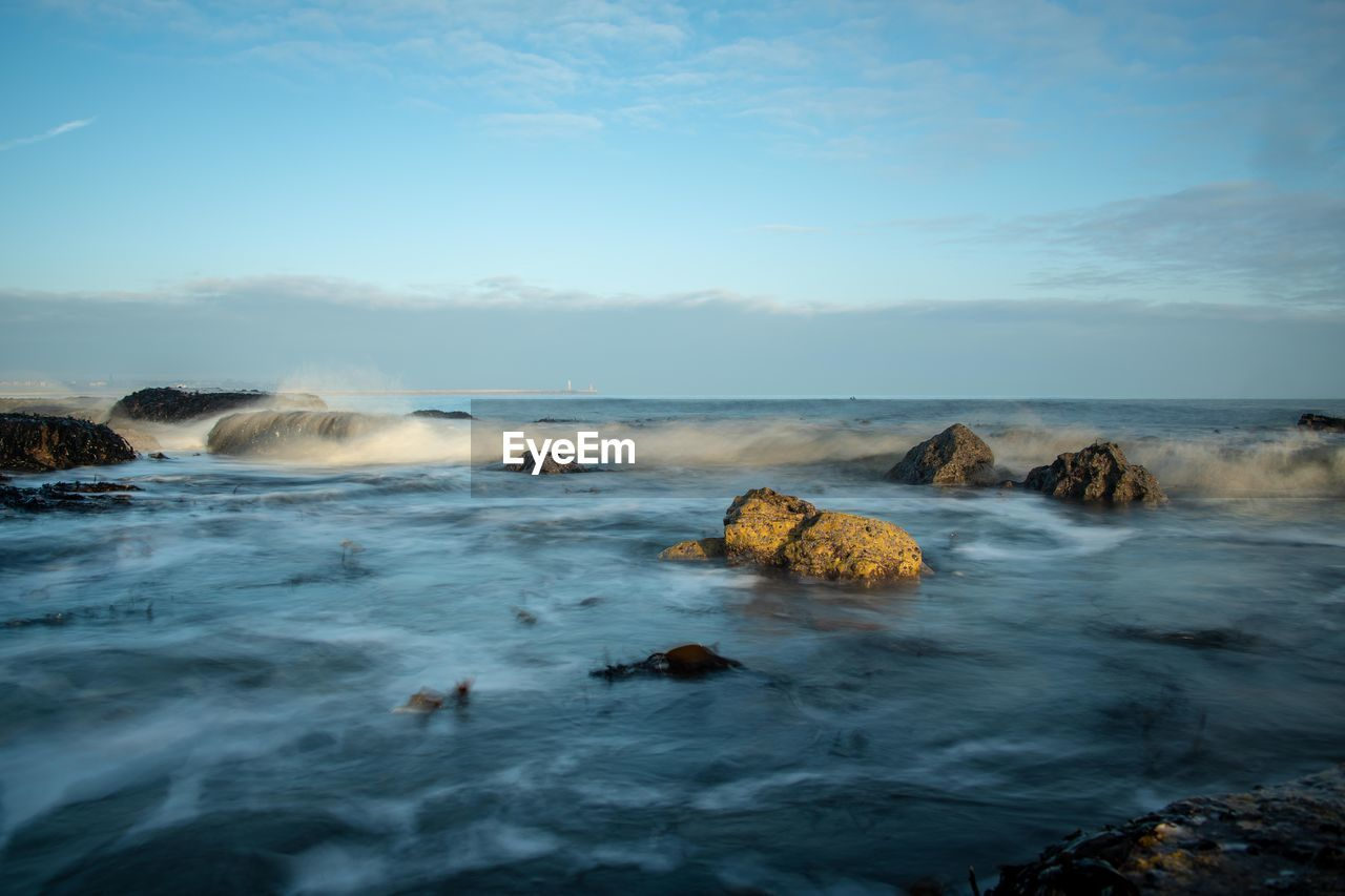 water, sea, motion, sky, beauty in nature, rock, scenics - nature, solid, wave, rock - object, nature, power in nature, land, long exposure, beach, blurred motion, splashing, no people, waterfront, outdoors, horizon over water