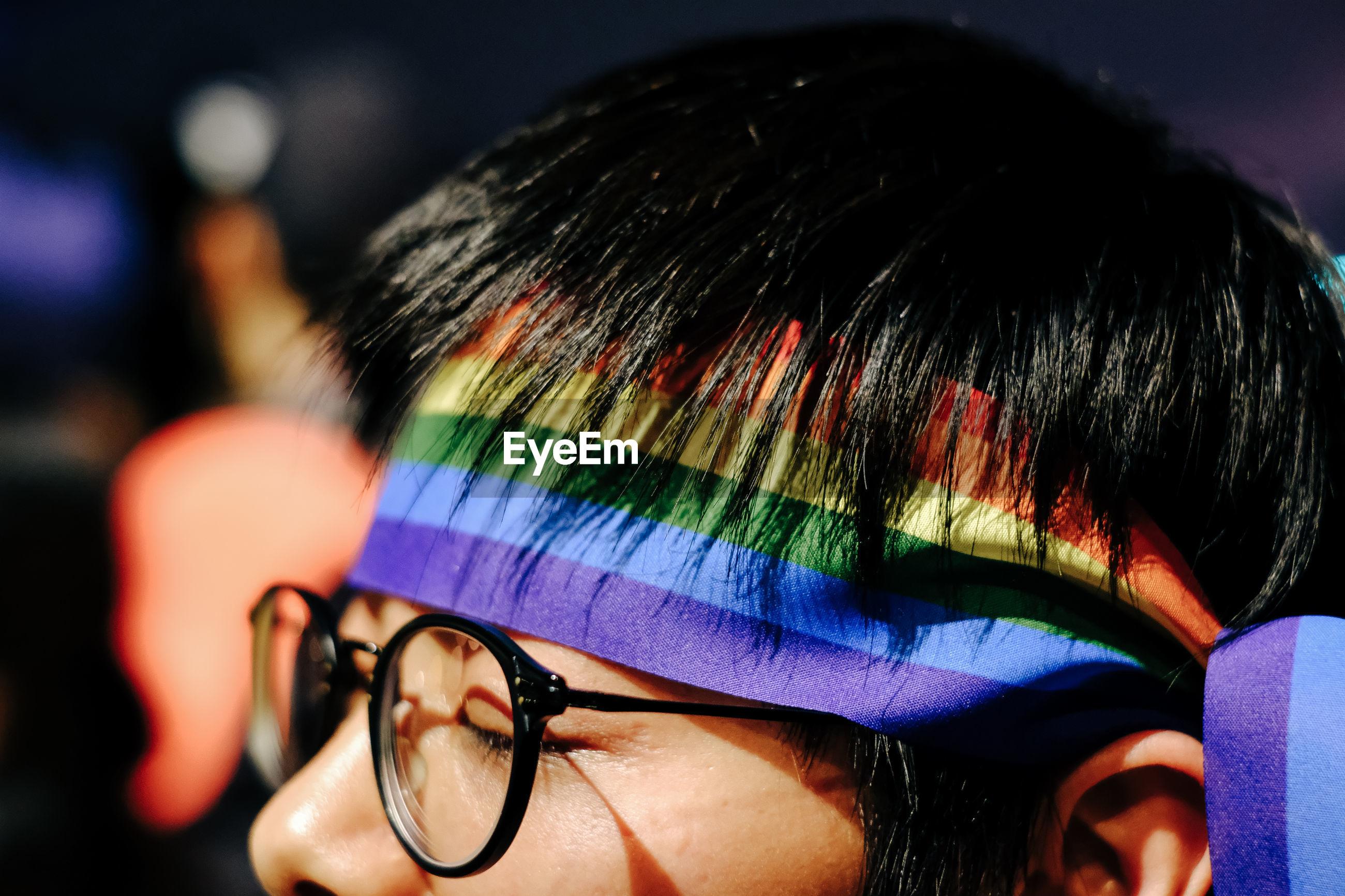 Close-up of gay man wearing rainbow flag