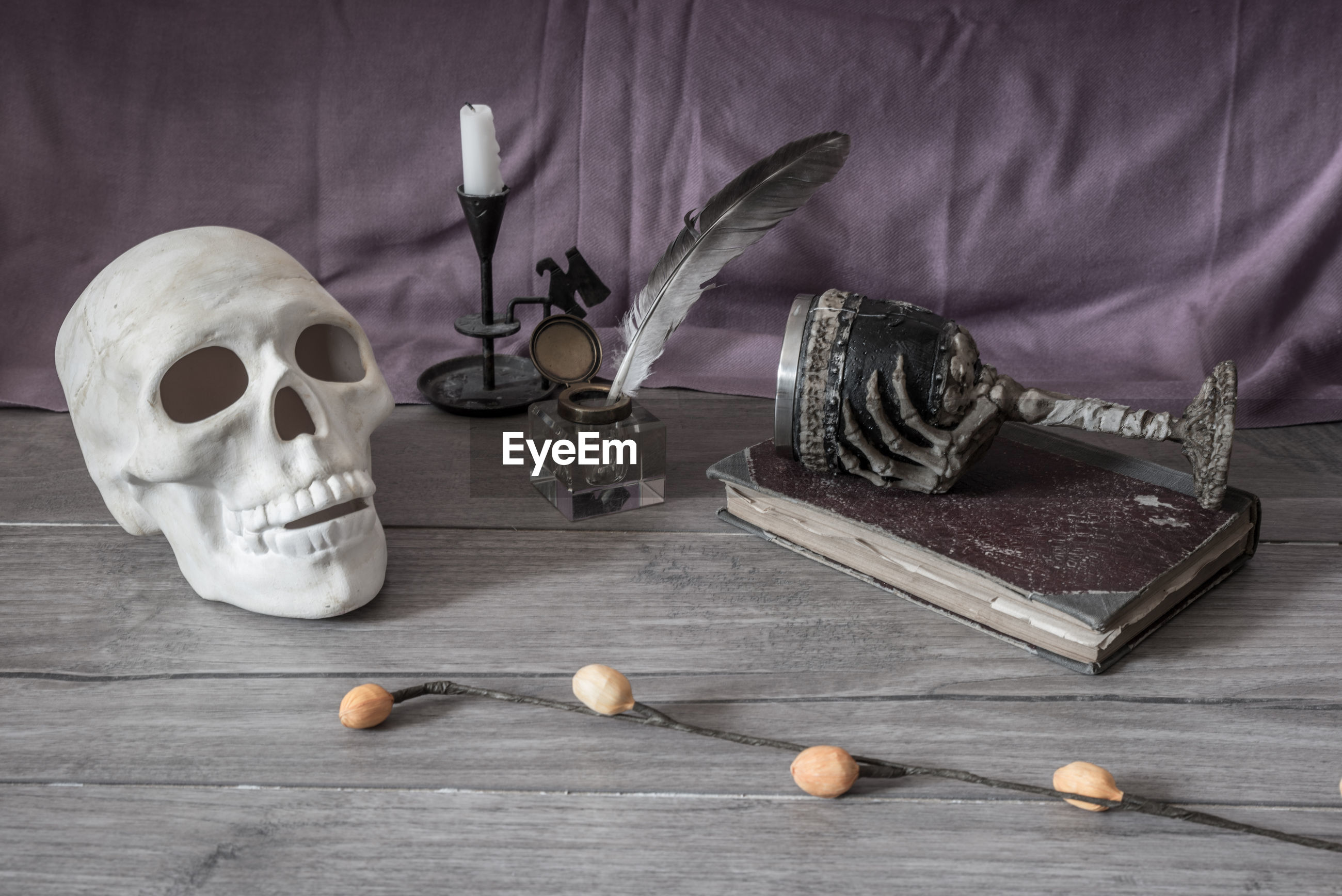 Skull with ink well and quill pen on table
