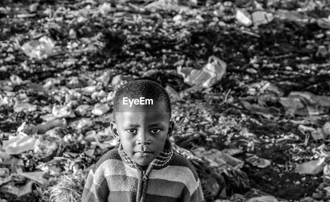 Portrait of boy against garbage