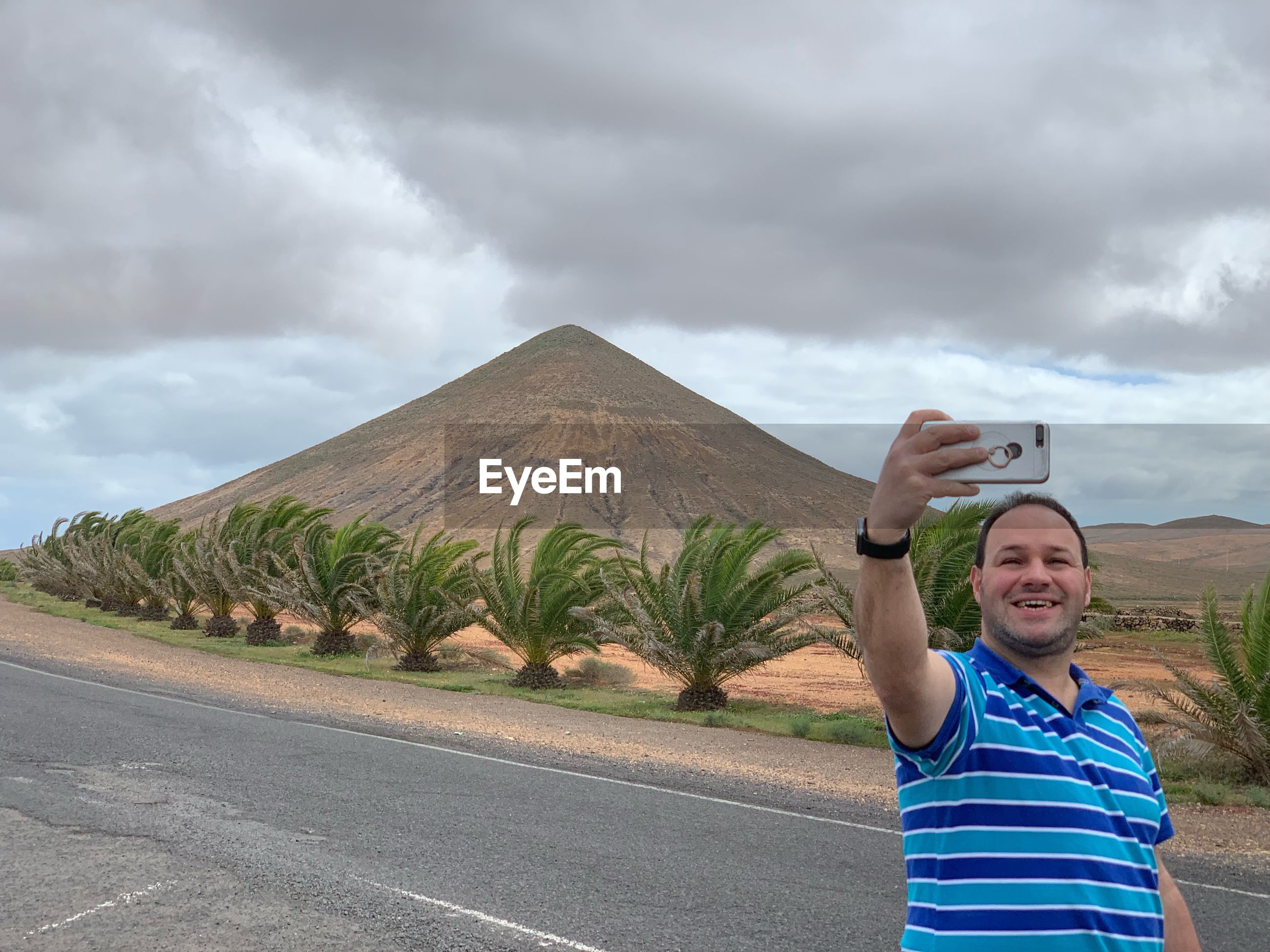 Smiling man taking selfie on mobile phone while standing on road against sky