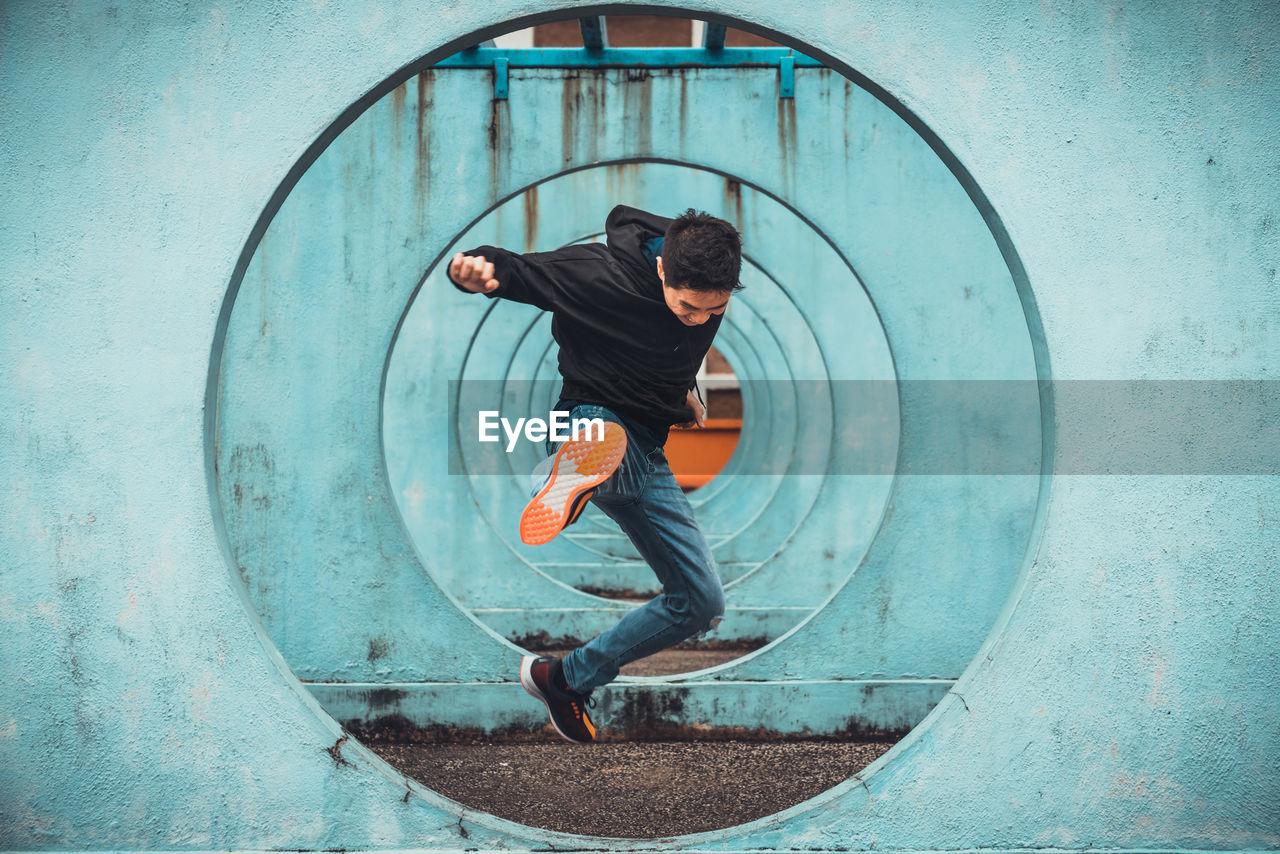 Man jumping through blue circles