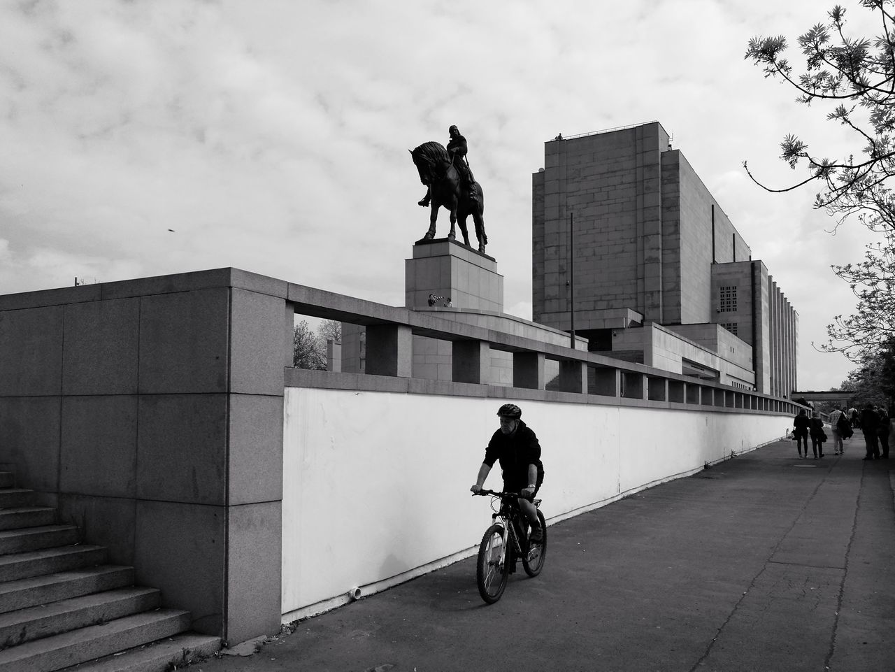 statue, architecture, art and craft, built structure, human representation, sculpture, bicycle, outdoors, day, sky, building exterior, men, real people, city, people