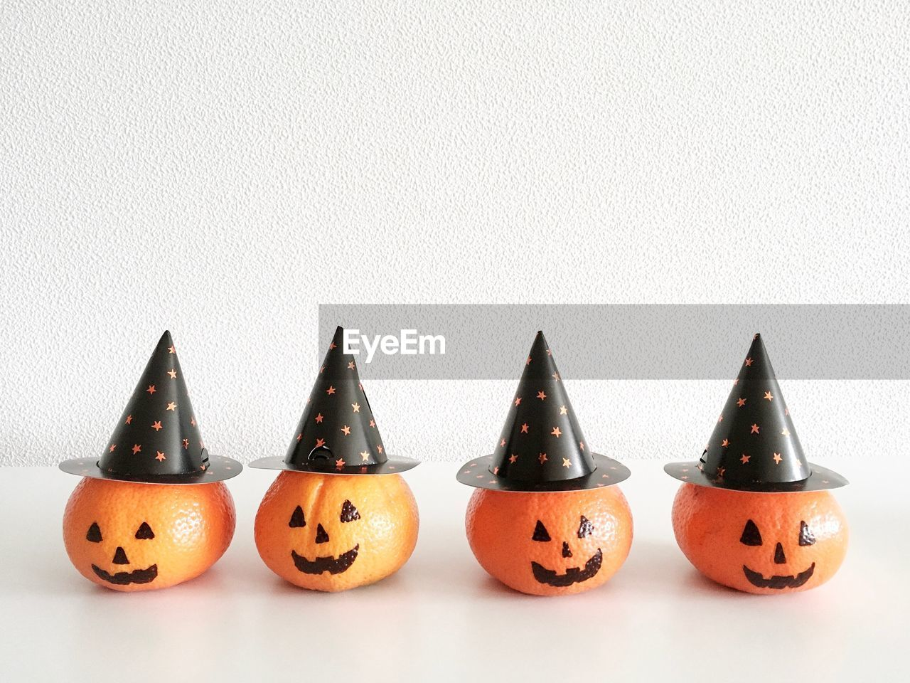 Close-up of pumpkin decorations with hat against white background