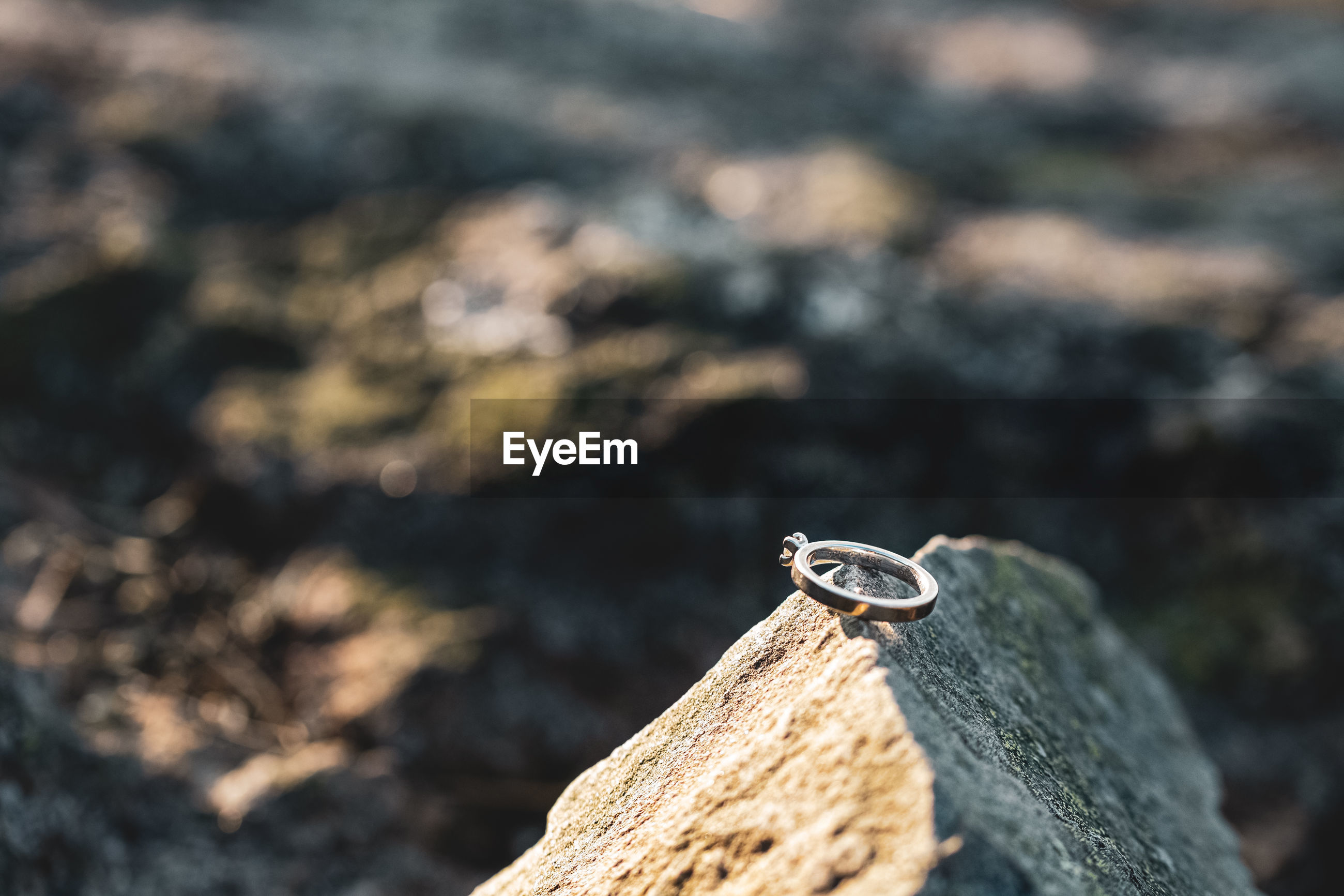 High angle view of wedding rings on rock