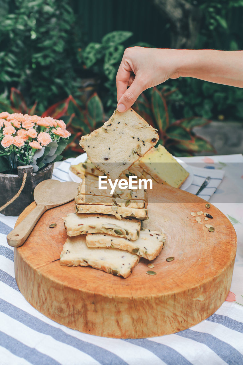 food and drink, food, human hand, hand, one person, human body part, freshness, bread, real people, holding, close-up, table, ready-to-eat, unrecognizable person, cheese, day, healthy eating, plate, baked, human limb, temptation