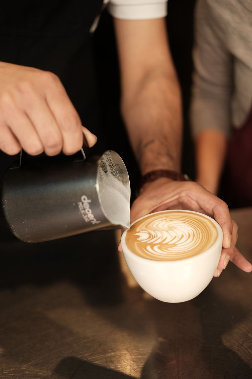 coffee - drink, food and drink, refreshment, drink, coffee, cup, coffee cup, mug, real people, frothy drink, cappuccino, froth art, cafe, holding, indoors, table, hot drink, men, still life, people, latte, hand, barista
