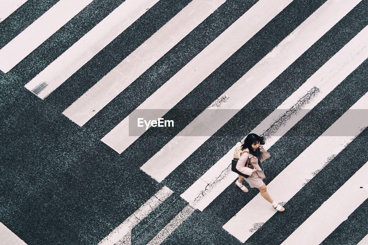 Aerial view of woman crossing zebra