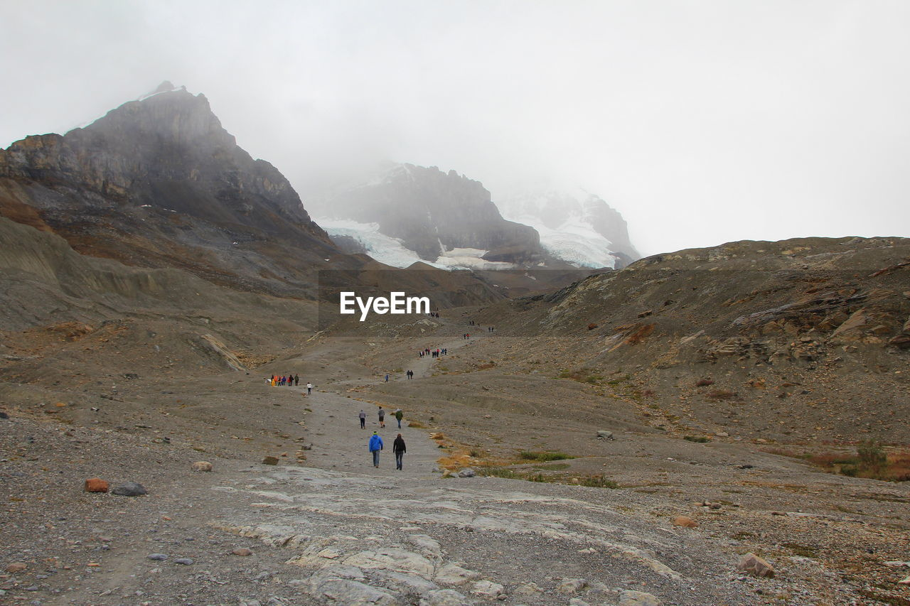 mountain, sky, landscape, beauty in nature, environment, leisure activity, group of people, hiking, nature, real people, adventure, mountain range, fog, people, scenics - nature, men, activity, day, incidental people, outdoors, mountain peak, formation