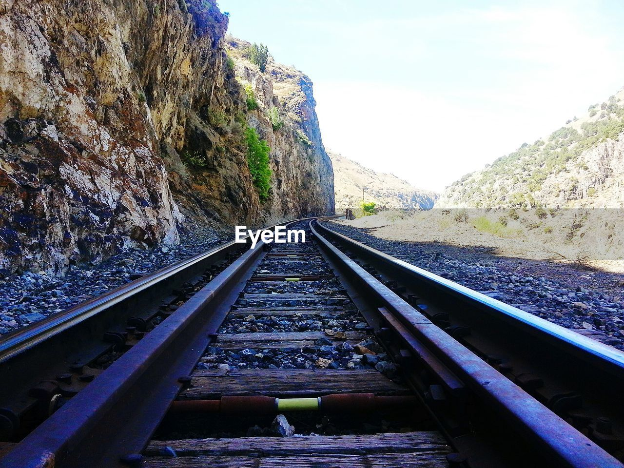 railroad track, transportation, rail transportation, day, rock - object, nature, no people, the way forward, tranquility, tranquil scene, beauty in nature, scenics, outdoors, mountain, landscape, sky