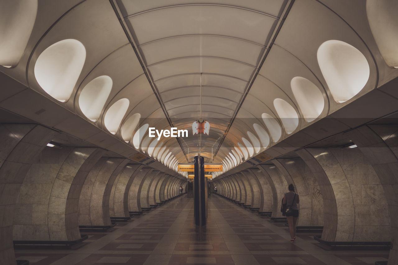 Rear View Of Woman Walking At Subway Station