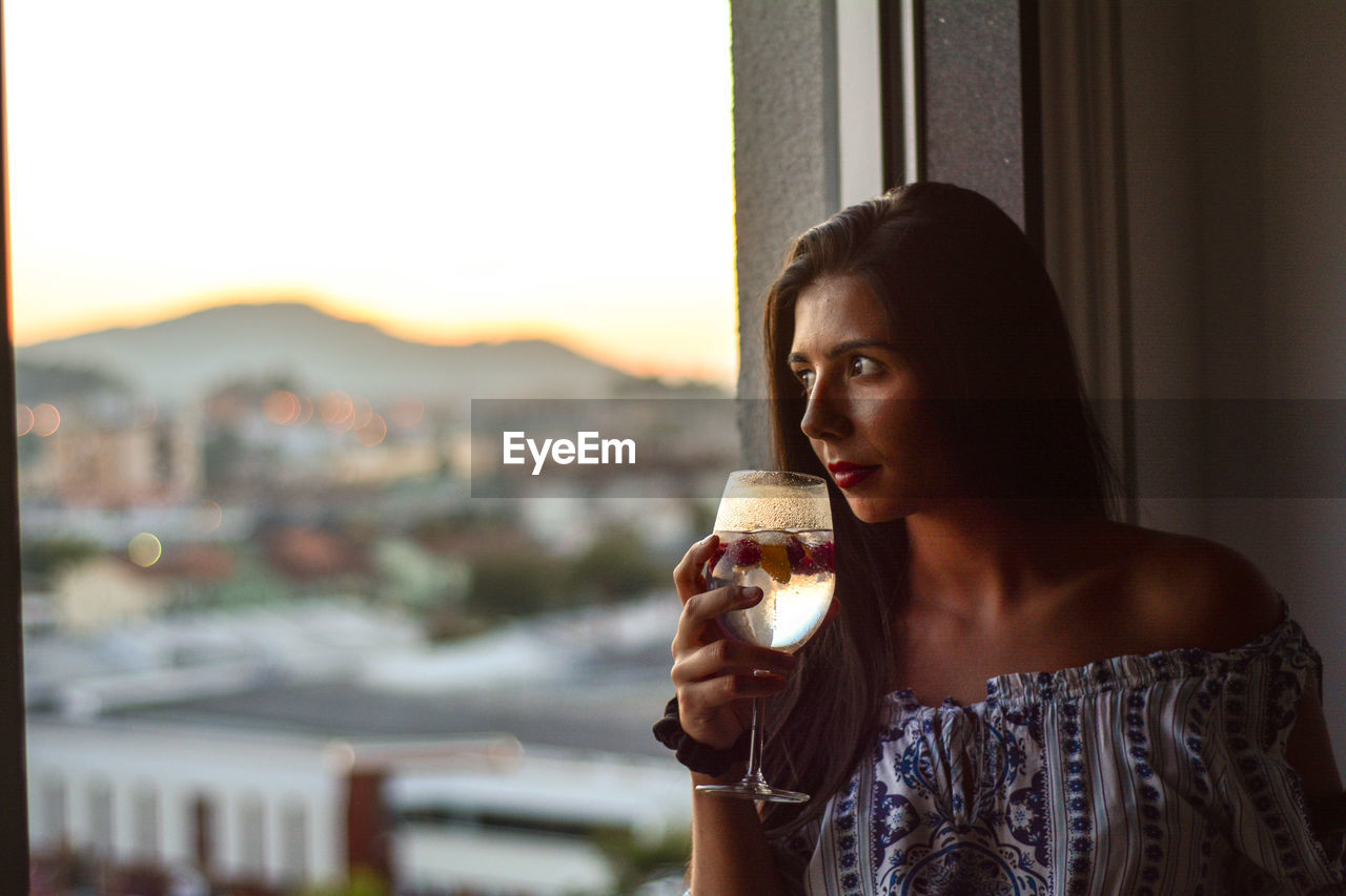 Thoughtful Young Woman Drinking Wine While Looking Through Window