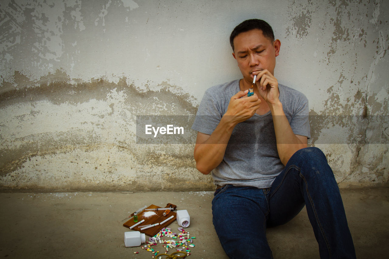 Mature Man Sitting By Narcotics Against Wall