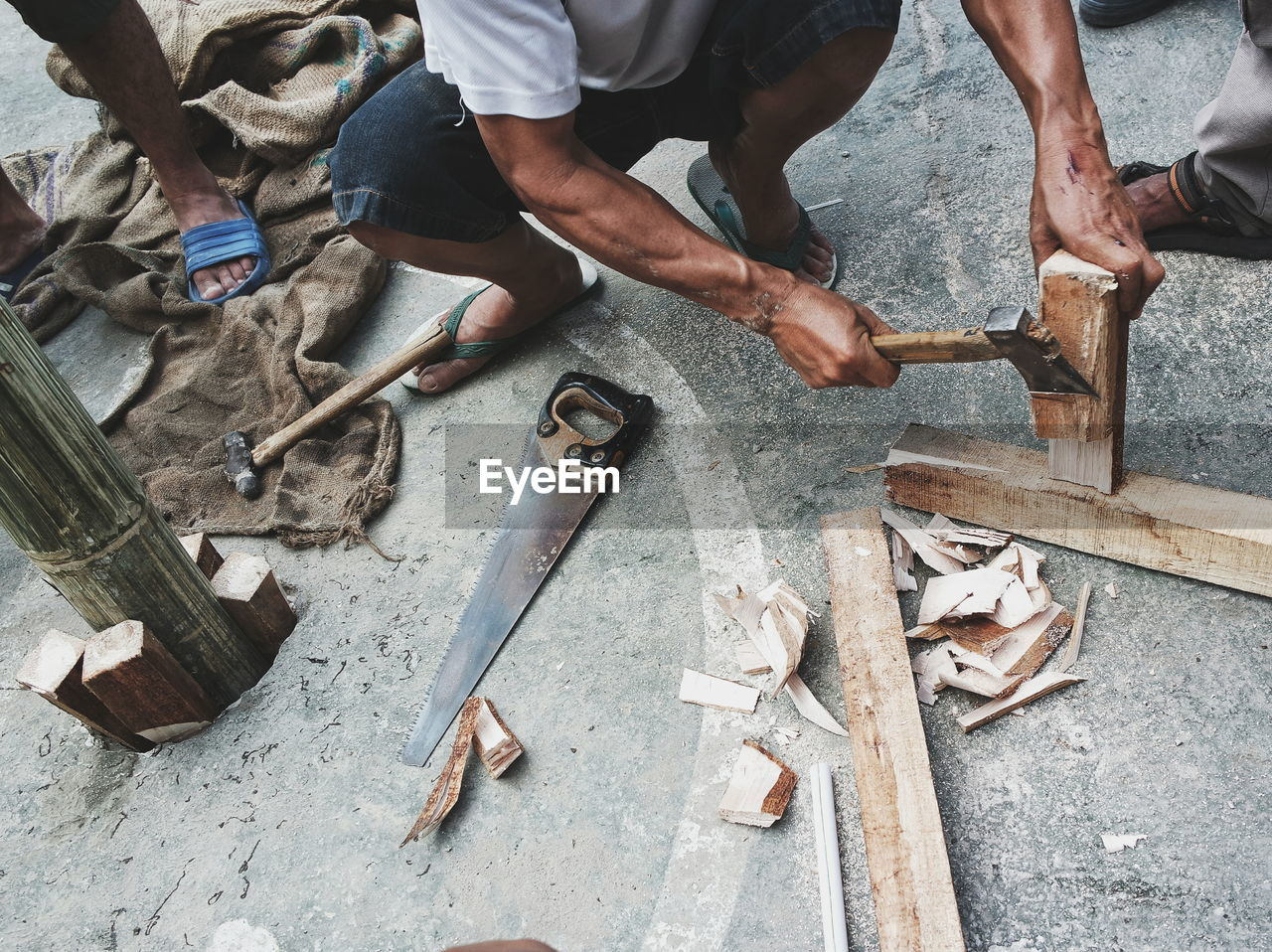 High angle view of man working with tools on wooden planks