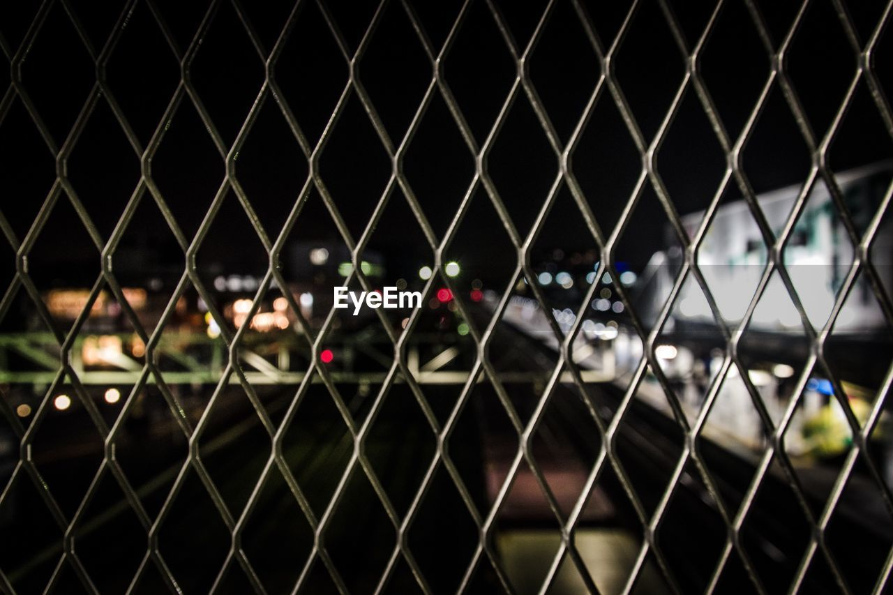 View Of Street Seen Through Chainlink Fence At Night