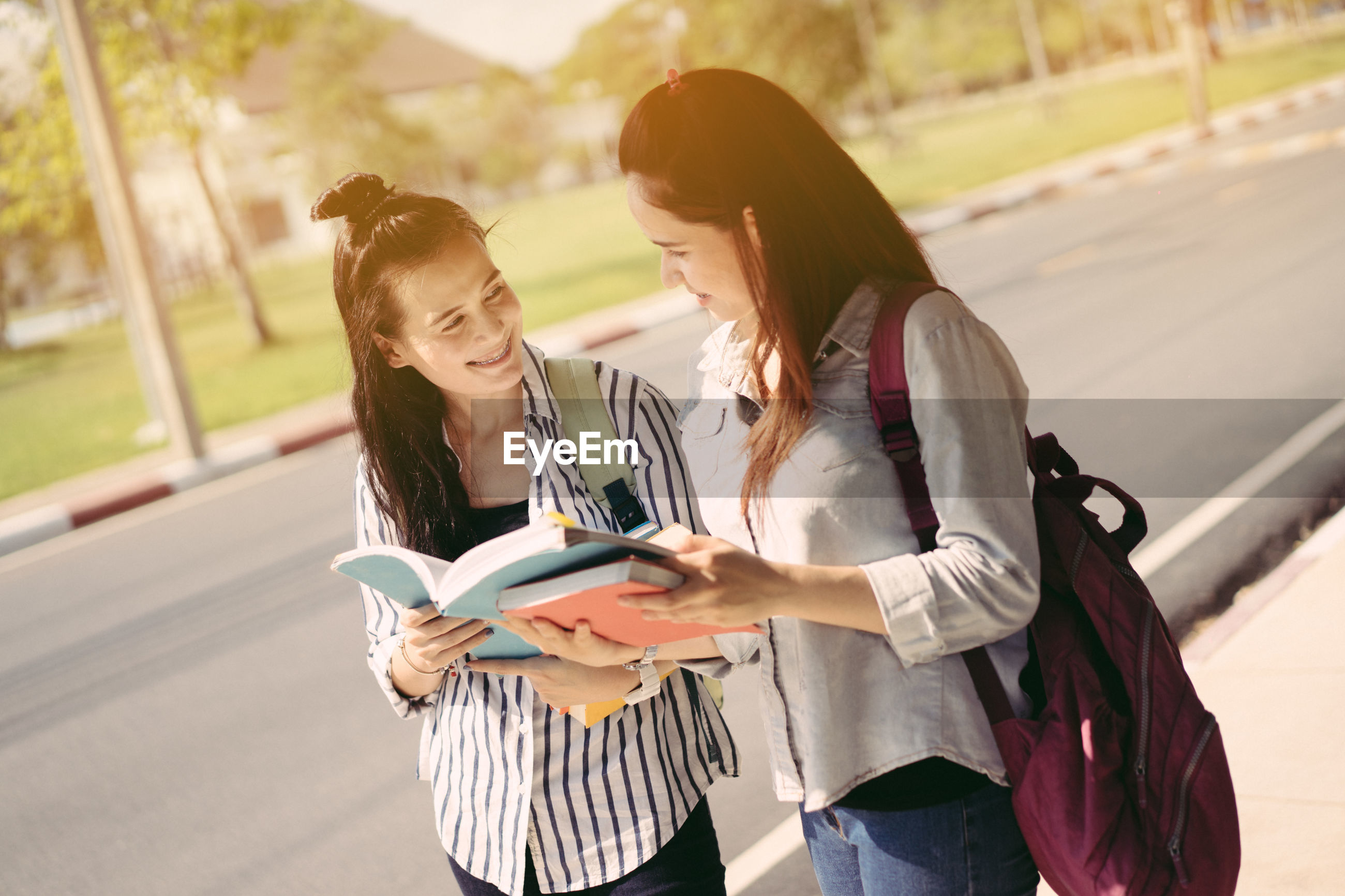 Young women standing with books on footpath at campus