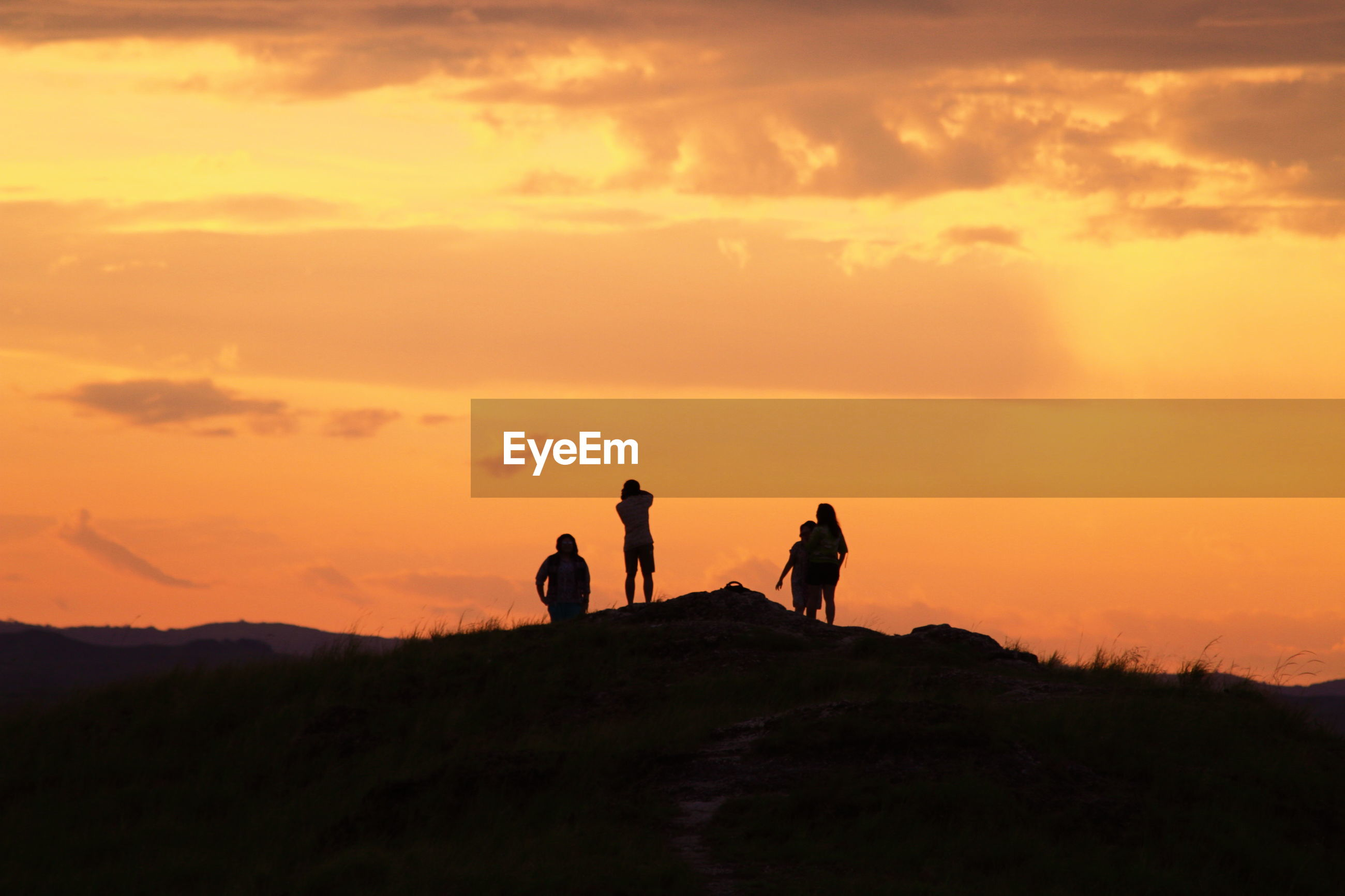 Silhouette people standing on mountain against orange sky