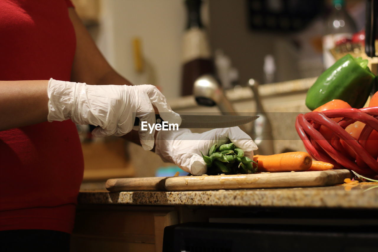 food and drink, vegetable, kitchen, cutting board, real people, food, indoors, human hand, healthy eating, hand, preparation, carrot, holding, freshness, kitchen knife, domestic kitchen, preparing food, domestic room, wellbeing, people, chef
