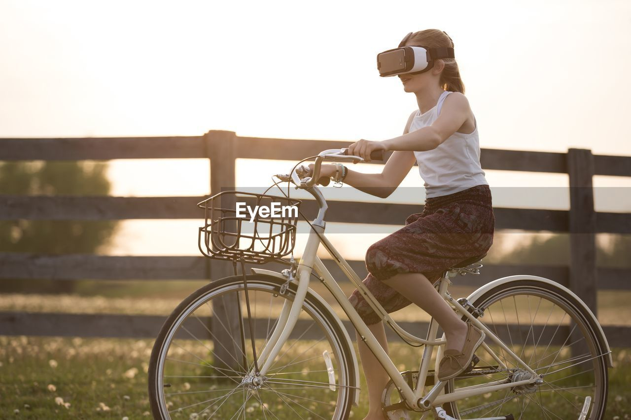 Woman using virtual reality simulator while riding bicycle on field